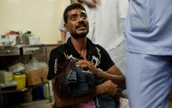 A father carries his wounded daughter to get medical help in Aleppo, Syria