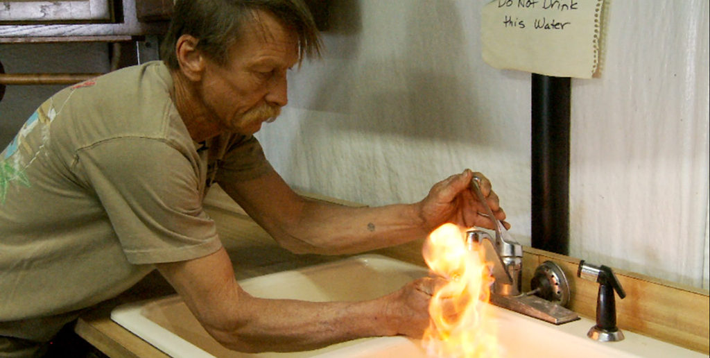 """Still from the documentary Gasland (2010) that shows flammable """"water"""" coming from a tap in a fracking area"""
