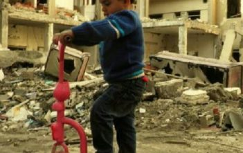 A child plays on a destroyed street in Homs, Syria
