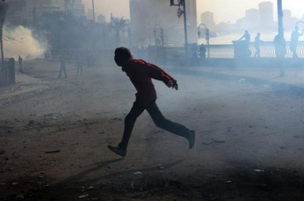 A protestor runs from tear gas in Egypt