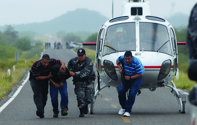 Police take a suspected drug trafficker off a helicopter in Mexico
