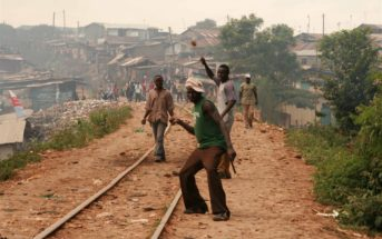 Rowdy youth throw stones in Kibera slums, Nairobi; Kenya