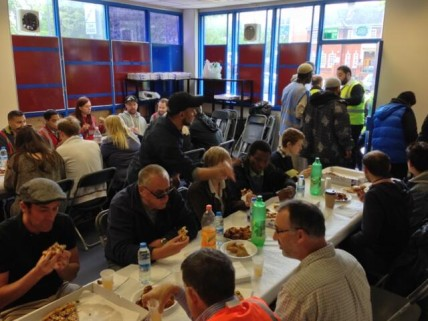People sit down to somosas and pizza at the Lewisham Islamic Centre