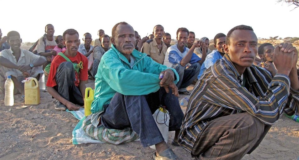 Migrants queue before being smuggled from Obock, Djibouti to Yemen